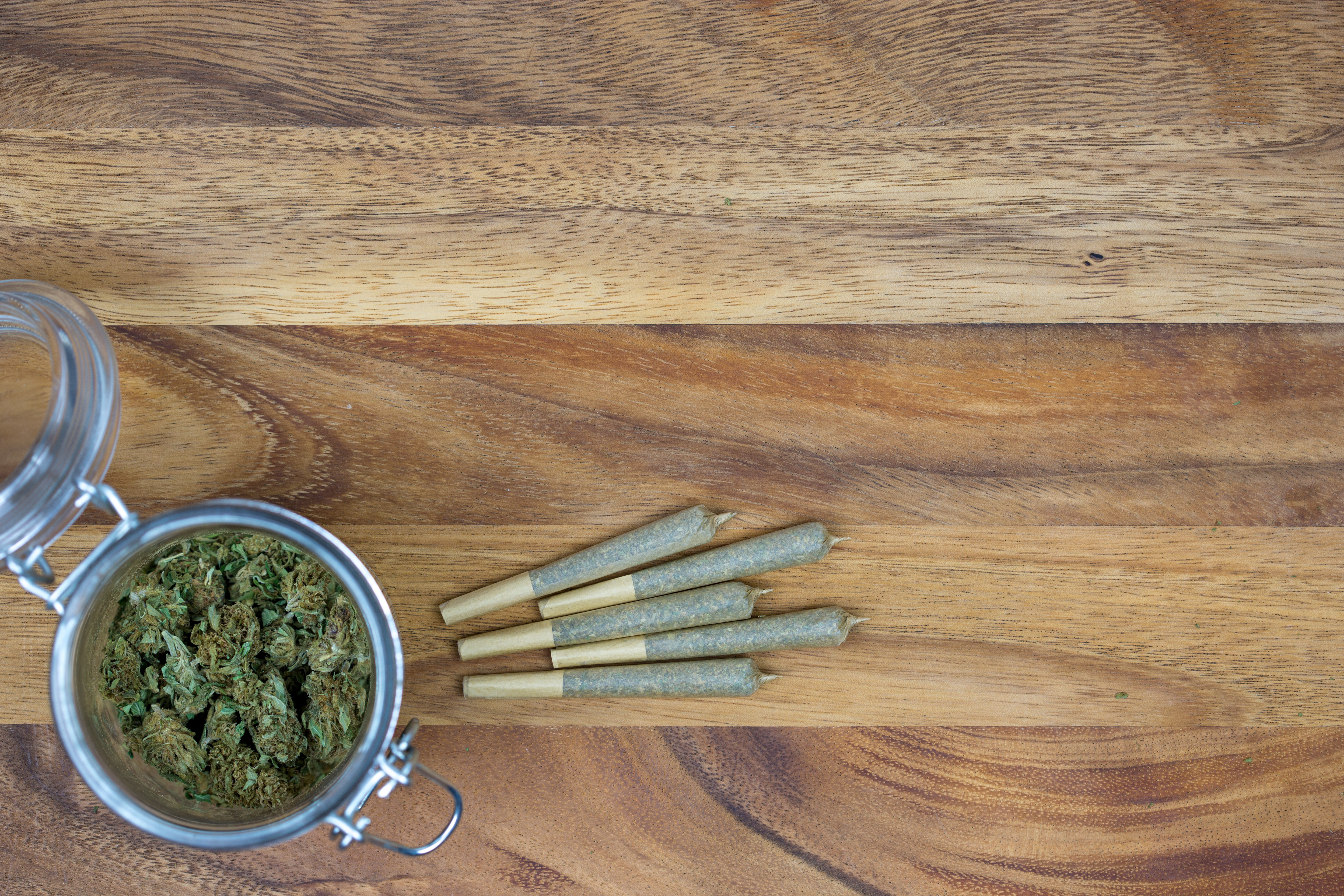 Weed in pot with joints on wooden surface