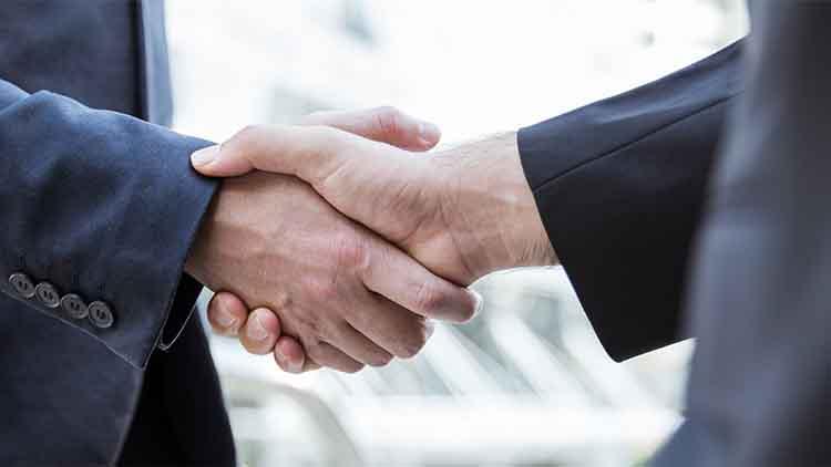 Closeup business caucasian man shaking hands in city.