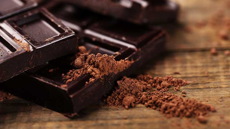 Dark chocolate with cocoa powder, on a wooden chopping board