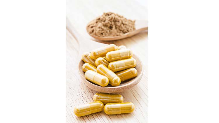 Herbal powder in capsule and spoon.