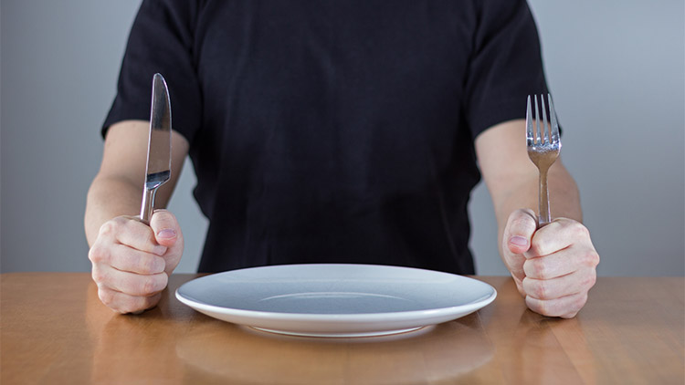 Man sitting at a table waiting for food, holding fork and knife