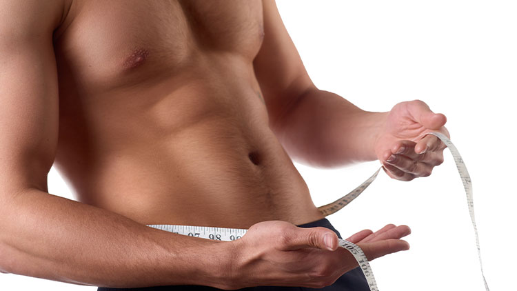 Man with a muscular body measuring his abs. Strong muscular man on isolated background