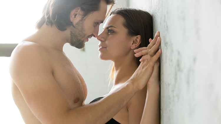 Sensual couple holding hands looking in the eyes leaning on wall