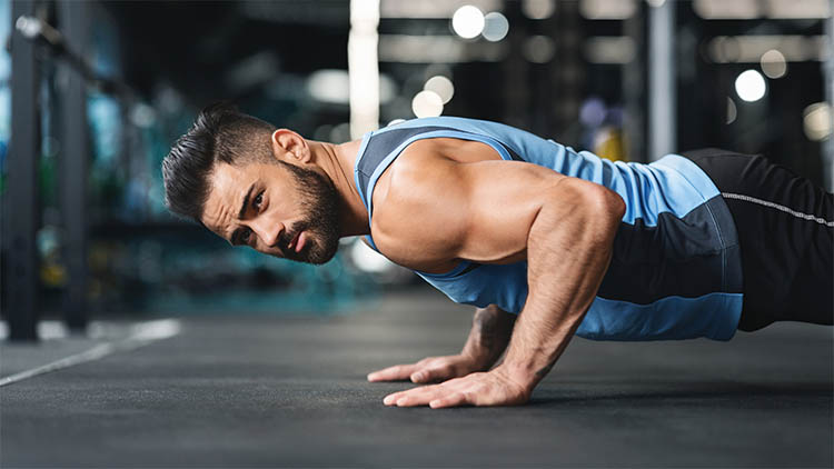 Strong caucasian guy making plank or push ups exercise,