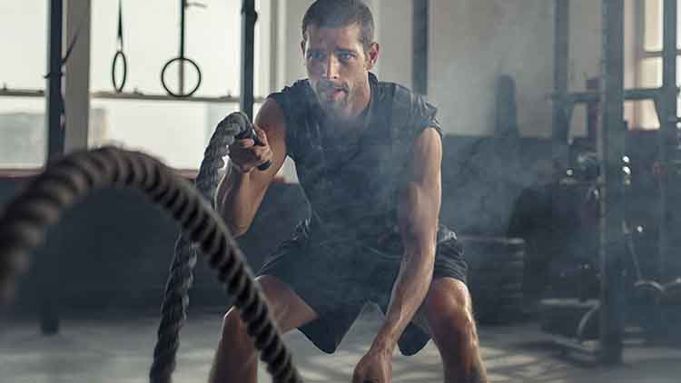 Young man exercising using battle rope