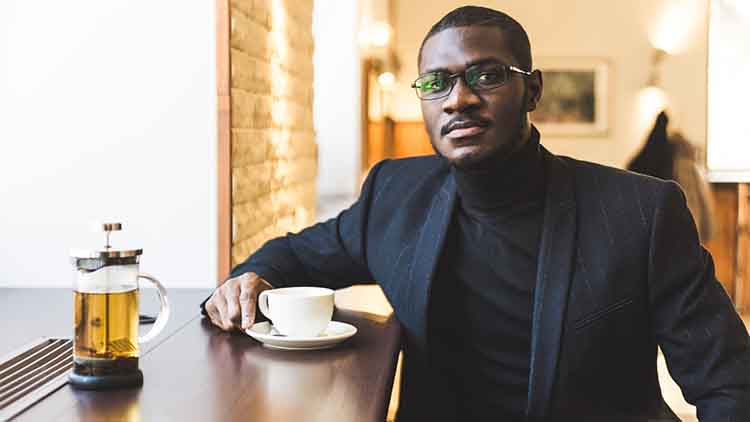 Young handsome dark-skinned businessman in a cafe with a cup of tea.