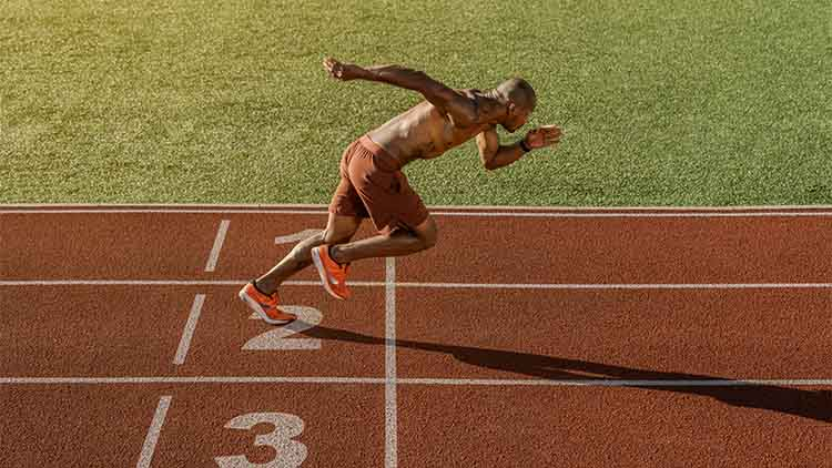 Young muscular athlete starting his running at the stadium track