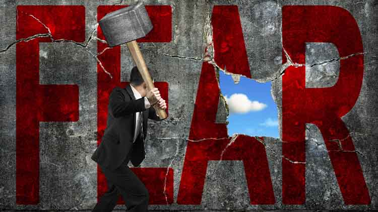 businessman holding hammer hitting red FEAR word on concrete wal