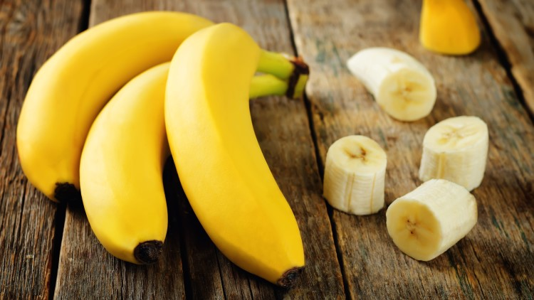 Chopped banana next to bananas on wooden table