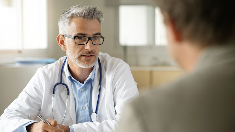 Doctor speaking with patient in office.