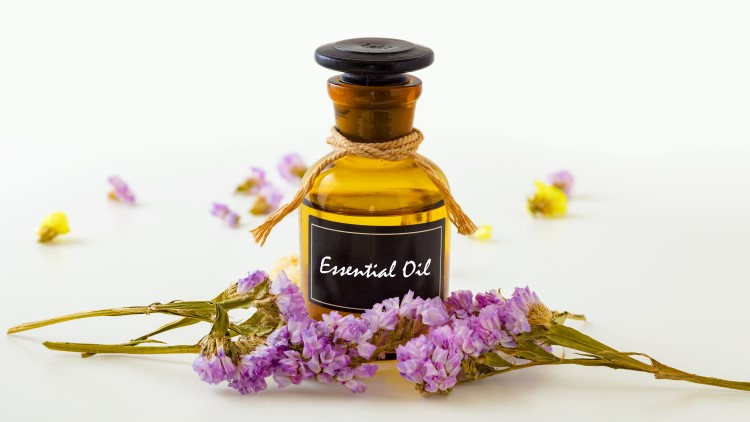 Essential oil bottle with flowers in front