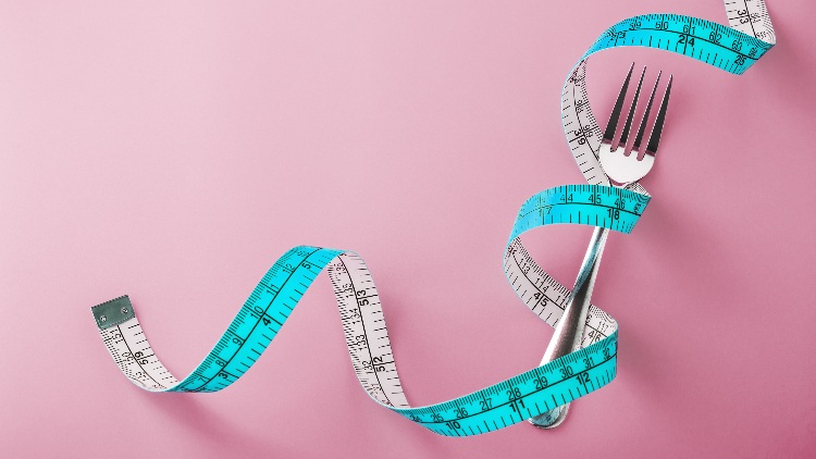 Fork with measuring tape around on pink background