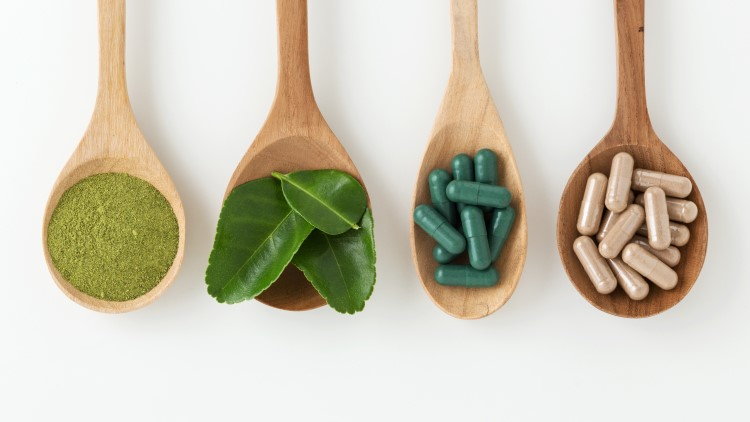 Herbal medicines on spoons on white background