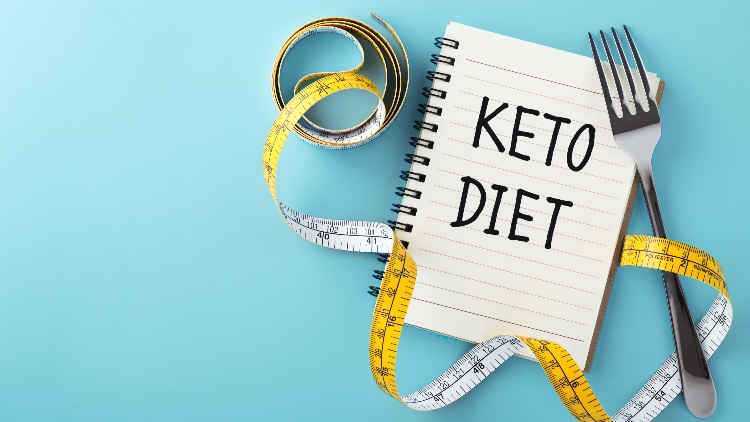 Keto diet written on note with fork and measuring tape on blue background