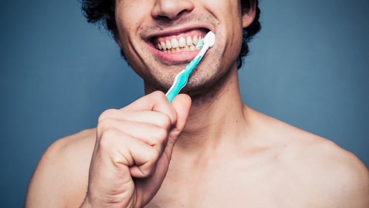 Man brushing teeth happily