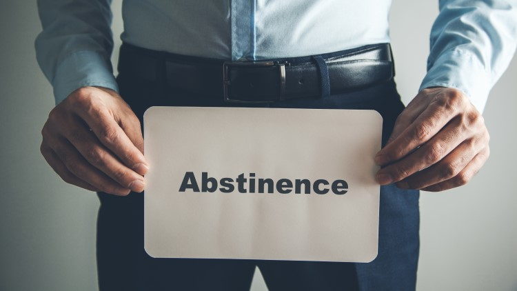 Man holding abstinence sign in front of groin