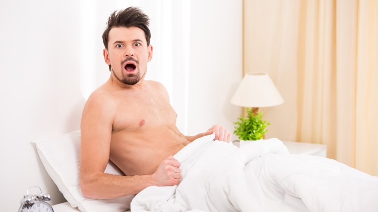 Man looking shocked topless in bed