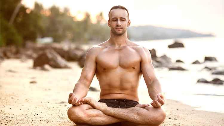man practicing yoga on the beach shirtless