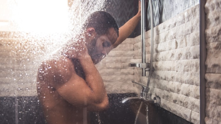 Man stood under shower looking down