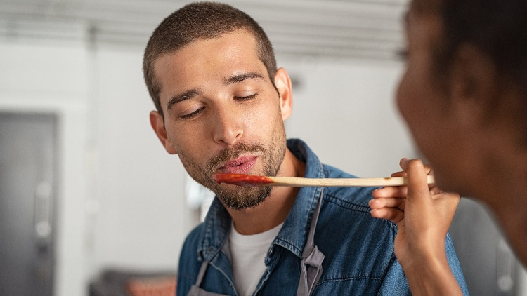 Man tasting tomato sauce from wooden spoon