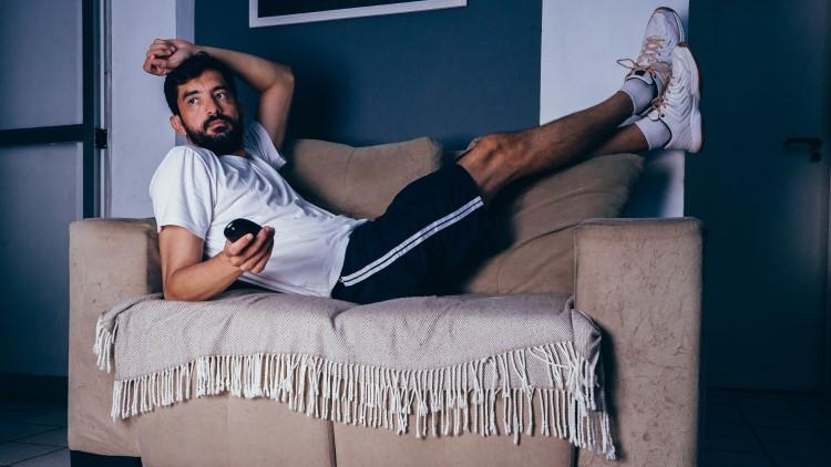 Man wearing sportswear watch tv on couch