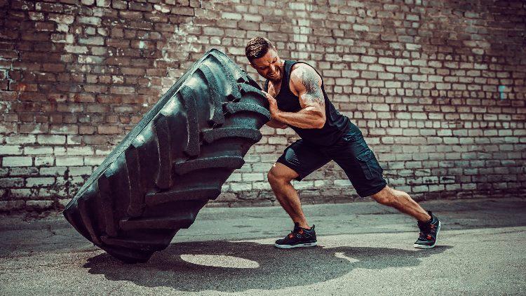 Muscular man flipping over huge tyre in street