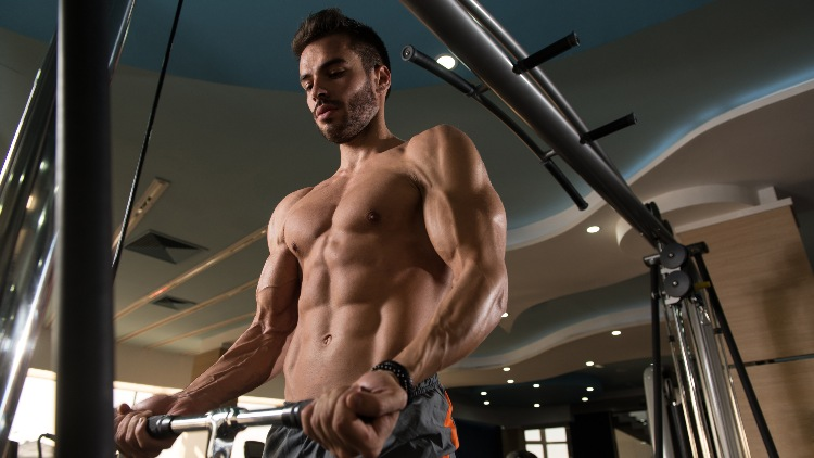 Muscular man in gym looking down at weights exercising biceps