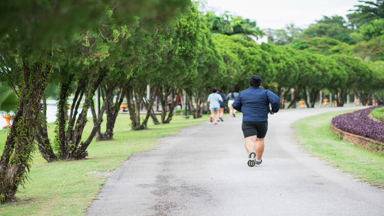An overweight man jogging in a park