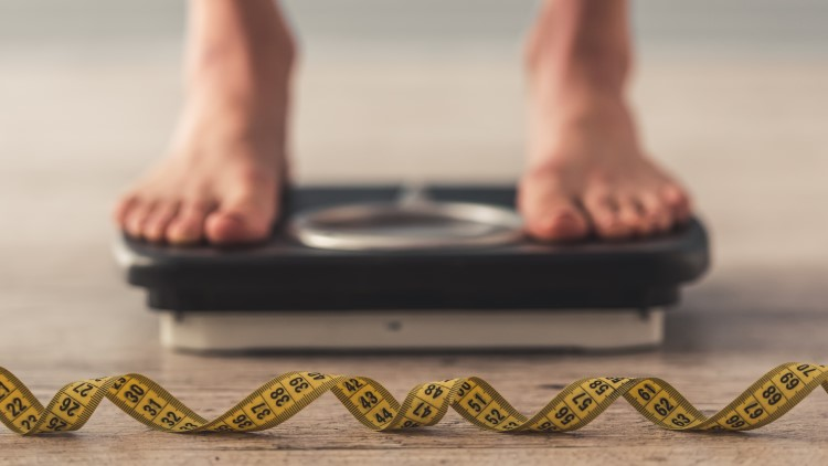 Person on weighing scales next to measuring tape