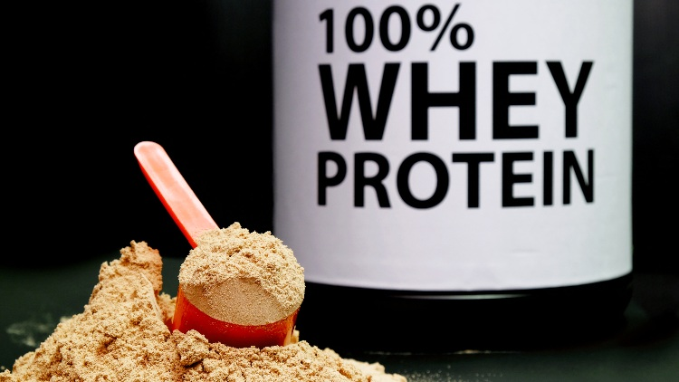 Pile of Whey protein in front of bottle