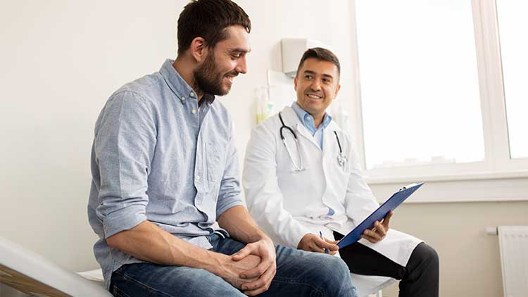 smiling doctor and young man meeting at hospital