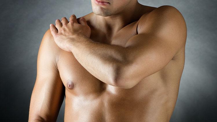 young male bodybuilder applying pain relief gel