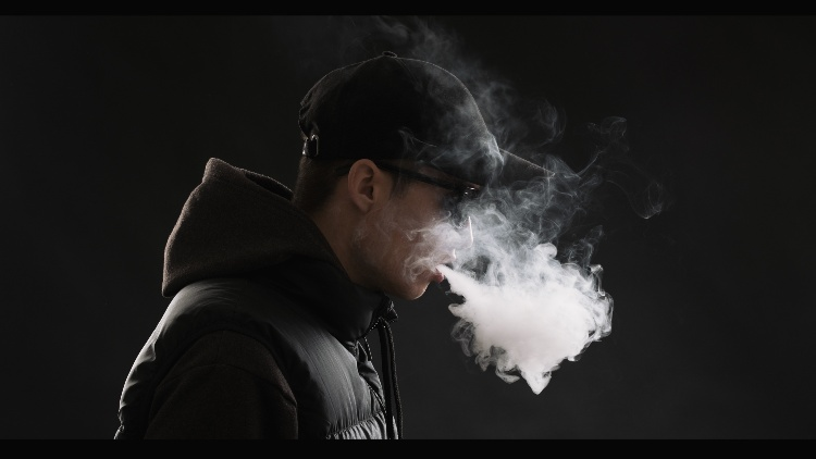 Young man blowing cloud of smoke black background