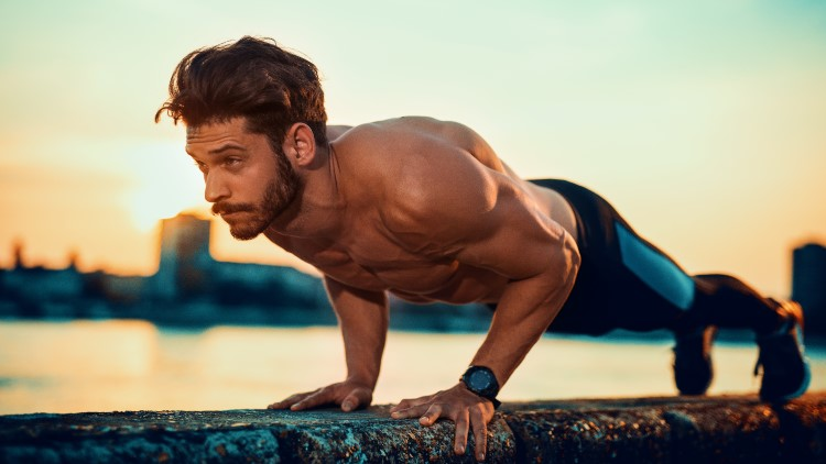 Young man doing pushups on wall