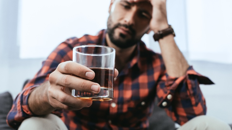 Young man looking depressed with glass of whisky in hand
